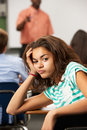 Bored female teenage pupil in classroom leaning on desk looking at camera Royalty Free Stock Photography