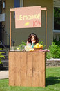 Bored girl at lemonade stand in front yard Royalty Free Stock Images