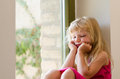 Bored girl with long blond hair sitting by the window Royalty Free Stock Photo