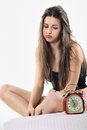 Bored girl looks at alarm clock blowing beautiful and blows unhappy wake up concept Royalty Free Stock Photos