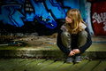 Bored girl sitting in front of a graffiti wall Royalty Free Stock Photos