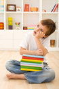 Bored kid with lots of school books Royalty Free Stock Images