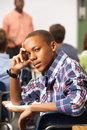 Bored male teenage pupil in classroom sitting down looking at camera Stock Image
