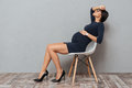 Bored pregnant business woman sitting over grey background. Royalty Free Stock Photo