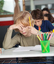 Bored schoolboy sitting at desk in classroom with hand on face Royalty Free Stock Image