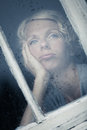 Bored woman looking at the rainy weather by the window frame Stock Photo