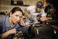 Bored woman with mechanic in background Royalty Free Stock Image
