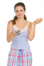 Bored woman in pajamas holding TV remote control Stock Photo
