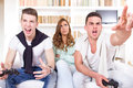 Bored women between two casual passionate men playing video game pretty with joystick at living room atmosphere Royalty Free Stock Image