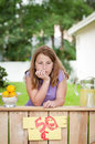Bored young girl with no customers at her lemonade stand a leans forward chin on hand Royalty Free Stock Photos