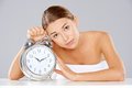 Bored young woman counting down the time sitting at a table clutching a large classic retro style silver metallic alarm clock with Royalty Free Stock Photo