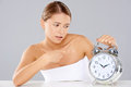 Bored young woman counting down the time sitting at a table clutching a large classic retro style silver metallic alarm clock with Royalty Free Stock Photography