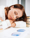 Bored young woman with many books and graphs education business concept indoors Stock Image