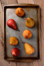 Bosc and red pears on baking sheet on wood table a group of a overhead view vertical format the is sitting a rustic wooden Royalty Free Stock Image