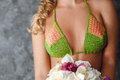 Bosom of blonde model in knitted bikini bouquet flowers Royalty Free Stock Images