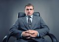 Boss in a chair young man suit looking straight ahead Royalty Free Stock Images