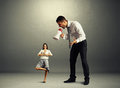 Boss screaming at small calm woman aggressive women over dark background Stock Photo