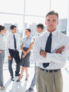 Boss standing with arms folded in a modern office colleagues behind Royalty Free Stock Photography