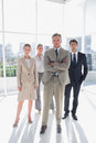 Boss standing with his arms folded with serious colleagues behind in a modern office Stock Images