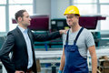 Boss and worker in factory young Stock Photos