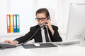 Bossy little businessman cheerful boy in formalwear talking on the phone while sitting at his working place Stock Photo