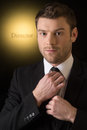 Bossy men young man adjusting his necktie while standing on black Royalty Free Stock Image