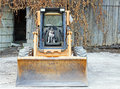 Boston terrier on the skid steer wants to drive at farm Stock Photos