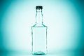 Bottle for alcohol isolated on a blue background Royalty Free Stock Image