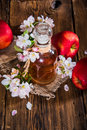 A bottle of apple cider vinegar (cider), fresh apples and apple-tree flowers on a wooden background. Royalty Free Stock Photo