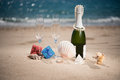 Bottle of champagne on the beach with a gift boxes and shells