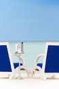 Bottle of champagne between chairs on beautiful sunny beach Stock Photos
