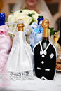 Bottle of champagne in costumes of bride and groom Stock Photos