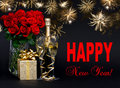 Bottle of champagne with golden fireworks and flowers happy new year card concept red roses gift beautiful on black background Stock Photo