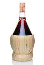 A bottle of chianti wine single with wicker basket base vertical format isolated on white with reflection Royalty Free Stock Photography