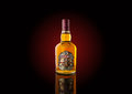Bottle of `Chivas Regal` whiskey with dark red backlight