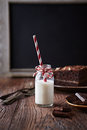 Bottle of cold milk with paper straw chocolate cake in background Royalty Free Stock Photography