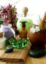 Bottle of essential oil, stones, mortar and flower Royalty Free Stock Photo