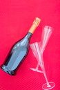 Bottle of fizz and glasses on red background close up Stock Photography