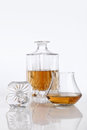 Bottle and glass of brandy on a white table background Royalty Free Stock Photo