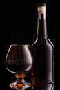 Bottle and glass of cognac over black background Royalty Free Stock Images