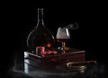 Bottle and glass of cognac with poker markers notebook and cigar in fire flame on black background Royalty Free Stock Images