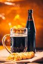 Bottle and glass of fresh dark beer with smoked cheese braid on sacking Royalty Free Stock Photo