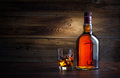 Bottle and glass of whiskey with ice on a wooden background Royalty Free Stock Photos