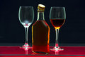 Bottle and glasses with alcohol one two of on the glass surface of the table Royalty Free Stock Photo