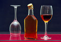 Bottle and glasses with alcohol one two of on the glass surface of the table Royalty Free Stock Image