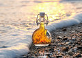 The bottle of Greek olive oil on the sea stony beach in the sea foamy wave Royalty Free Stock Photo