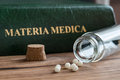 A bottle of homeopathic remedies with a materia medica Royalty Free Stock Photo