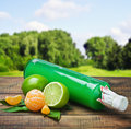 Bottle with the juice of citrus and lime on a background of nature Stock Photos