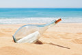 A bottle with a letter of distress on the beach summer Stock Photo