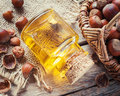 Bottle of nut oil and basket with filberts on old kitchen table. Royalty Free Stock Photo